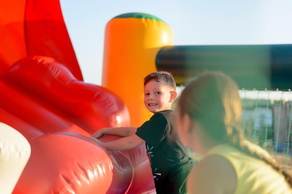 Two children playing on red bouncy castle
